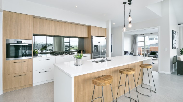 A waterfall-end island, natural-look cabinetry and plenty of countertop, cuisine classique, interior design, kitchen, real estate, white, gray