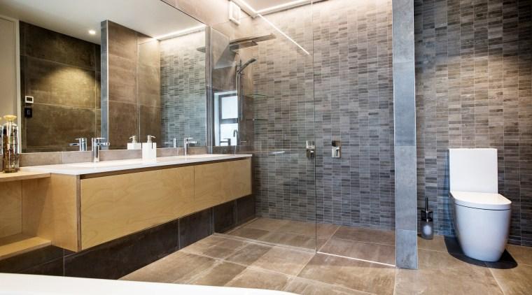 Cantilevering the long vanity allows for maximum countertop bathroom, floor, home, interior design, room, tile, wall, gray
