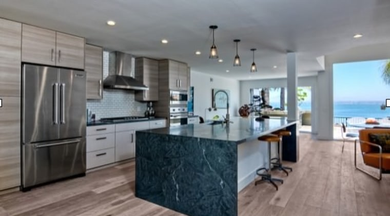 A waterfall island provides space for food prep cabinetry, countertop, cuisine classique, floor, flooring, hardwood, interior design, kitchen, real estate, room, wood flooring, gray