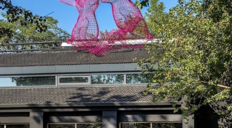 Two pink rabbits sit atop one of the architecture, building, facade, home, house, outdoor structure, plant, real estate, residential area, sky, tourist attraction, tree, black