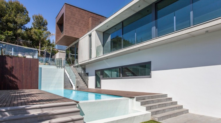 The home looks out to the garden – apartment, architecture, building, condominium, daylighting, estate, facade, home, house, property, real estate, residential area, swimming pool, villa, window, gray