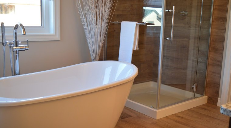 This freestanding tub makes the bathroom feel significantly bathroom, bathtub, floor, flooring, interior design, plumbing fixture, room, tile, brown, gray