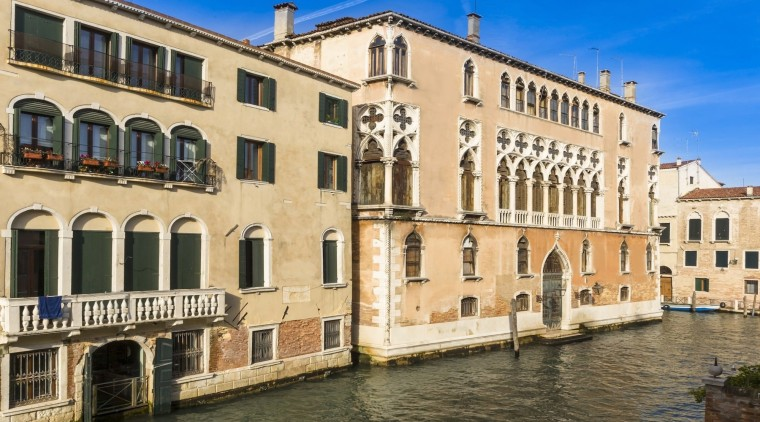 It's been owned by famous noble families from apartment, building, canal, channel, city, classical architecture, facade, historic site, medieval architecture, palace, plaza, property, real estate, town, waterway, window, orange, brown