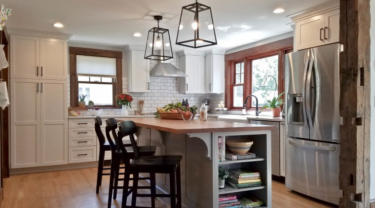 Two pendant lights sit above the island, drawing cabinetry, ceiling, countertop, cuisine classique, dining room, floor, flooring, hardwood, interior design, kitchen, laminate flooring, room, wood flooring, gray