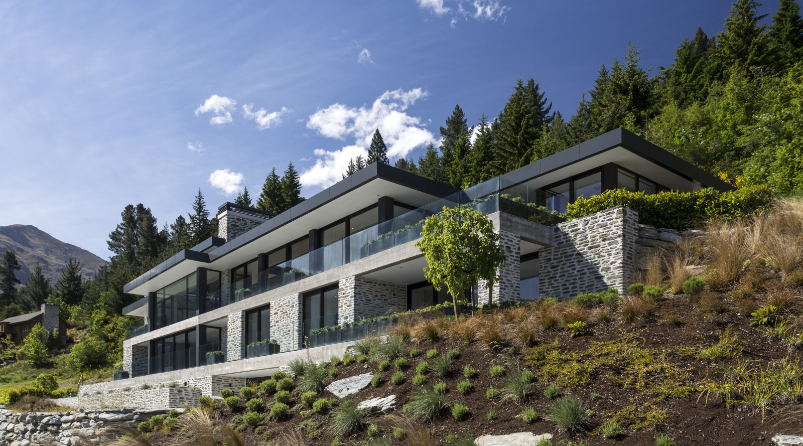 Large house on difficult steep slope is partly dug trends