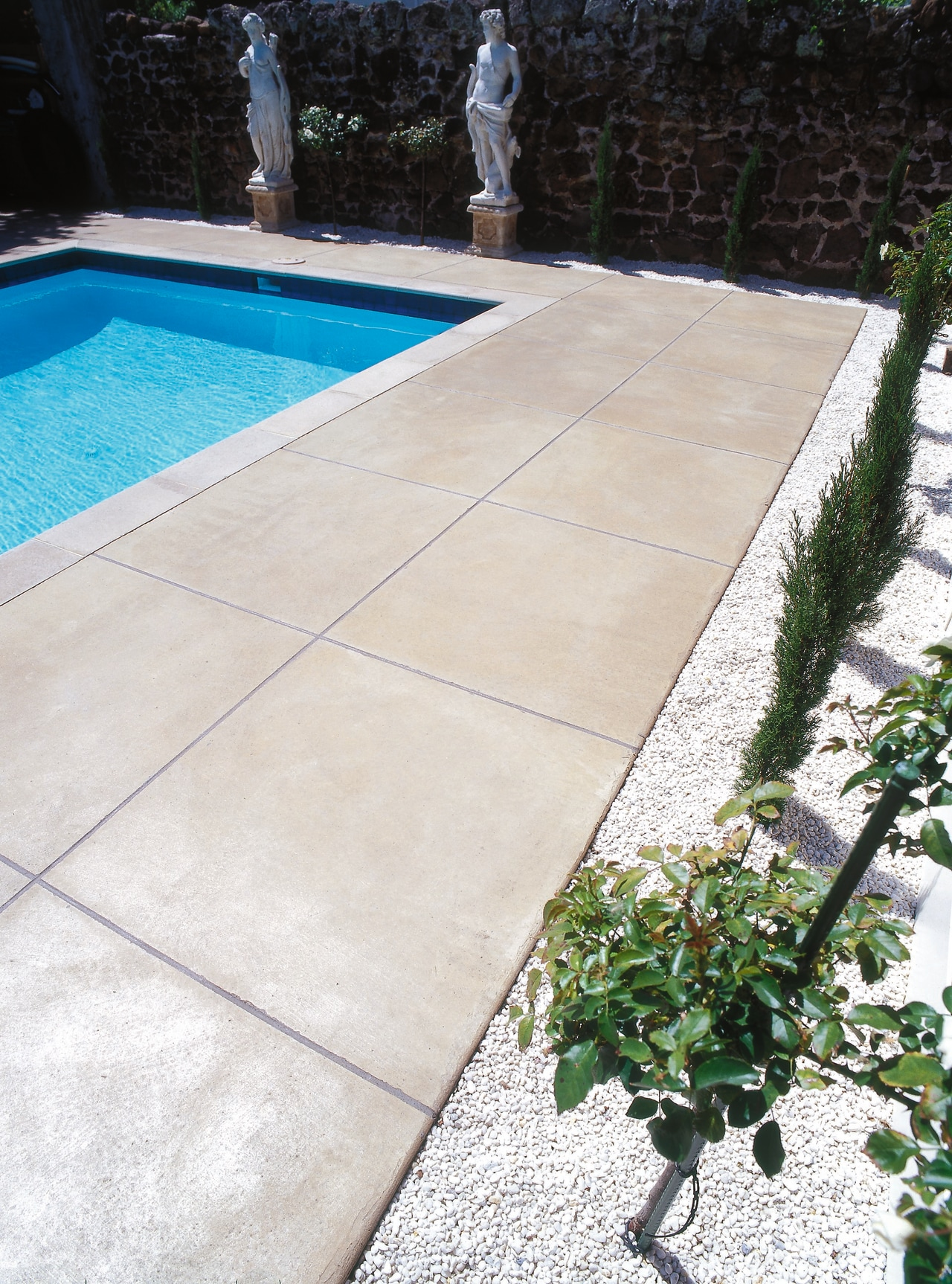 View of the homes exterior pool, garden and backyard, concrete, flagstone, floor, flooring, road surface, tile, walkway, wall, yard, white