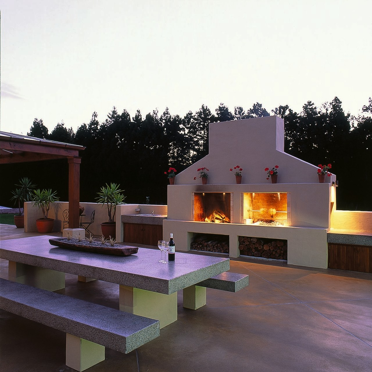 A view of a patio and fireplace of backyard, fireplace, home, house, outdoor structure, patio, real estate, residential area, roof, white, black