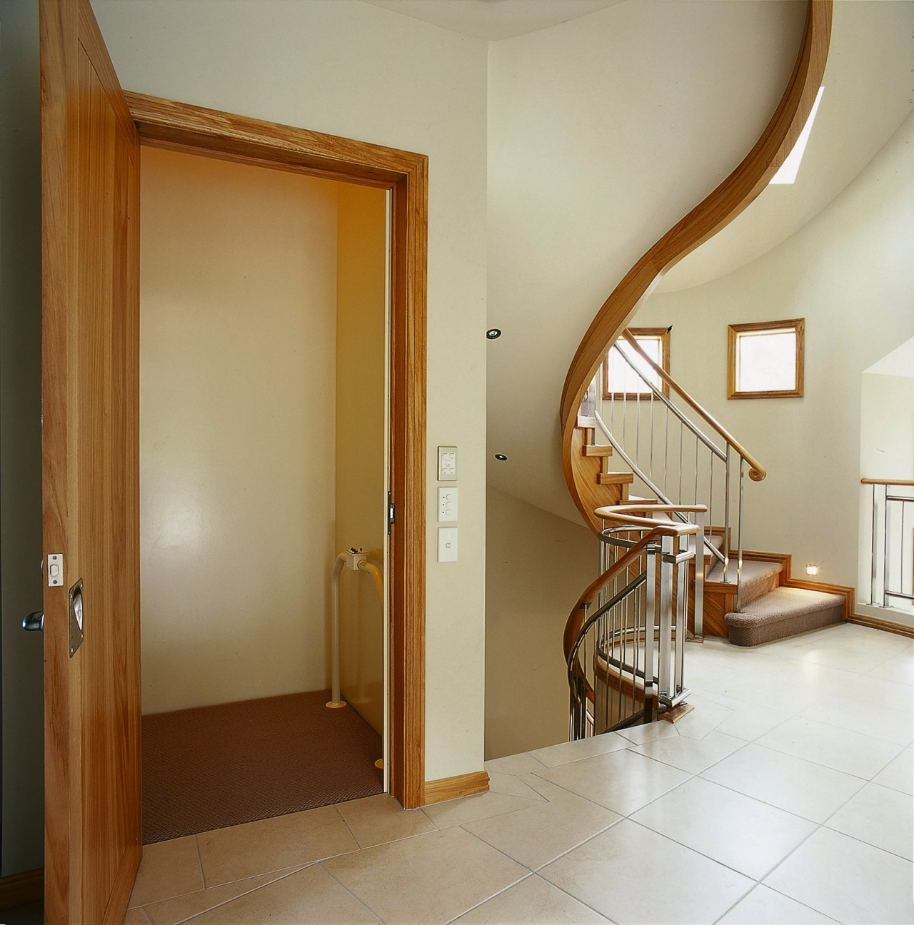 A photograph of an elevator on the second architecture, ceiling, door, floor, flooring, hardwood, home, interior design, property, real estate, room, stairs, wall, window, wood, wood flooring, brown, orange
