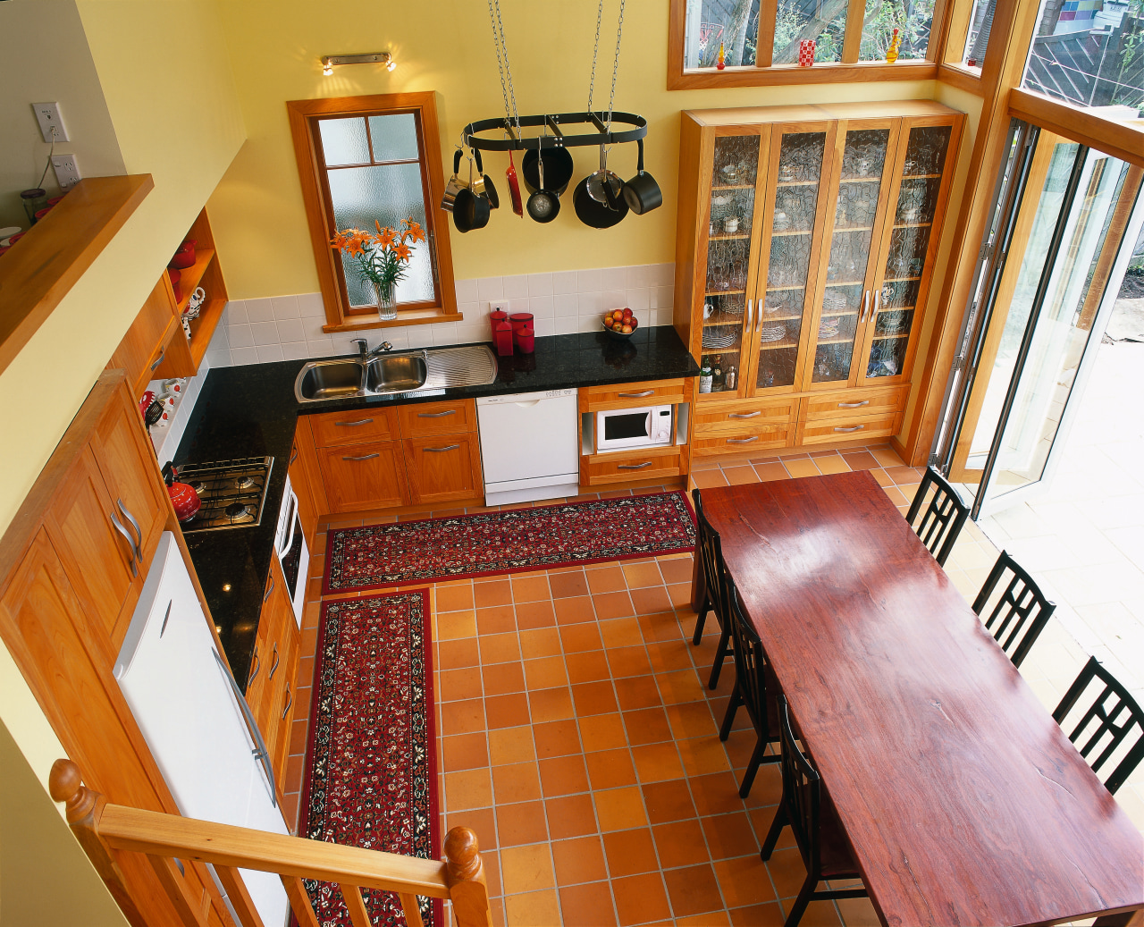 View looking down at kitchen with black granite dining room, floor, flooring, furniture, hardwood, home, house, interior design, kitchen, living room, property, real estate, room, stairs, table, wood, brown
