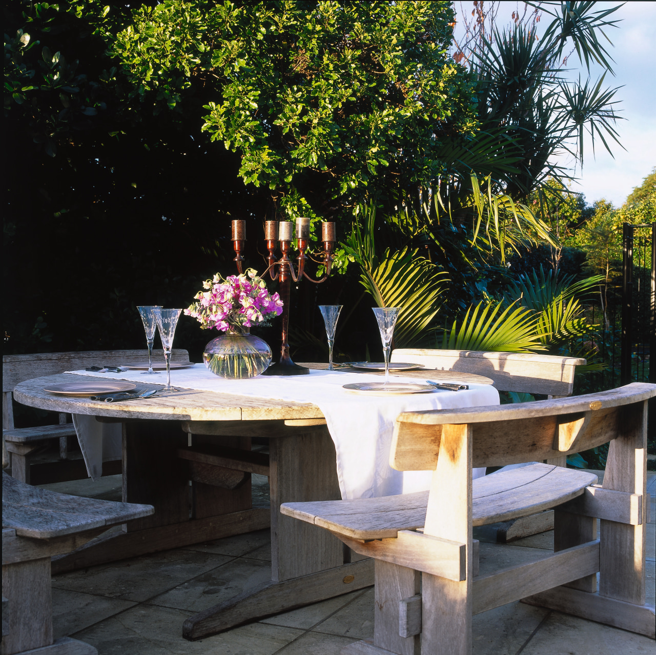 This quaint table setup can be ruined backyard, bench, chair, furniture, outdoor furniture, outdoor structure, patio, plant, table, tree, black