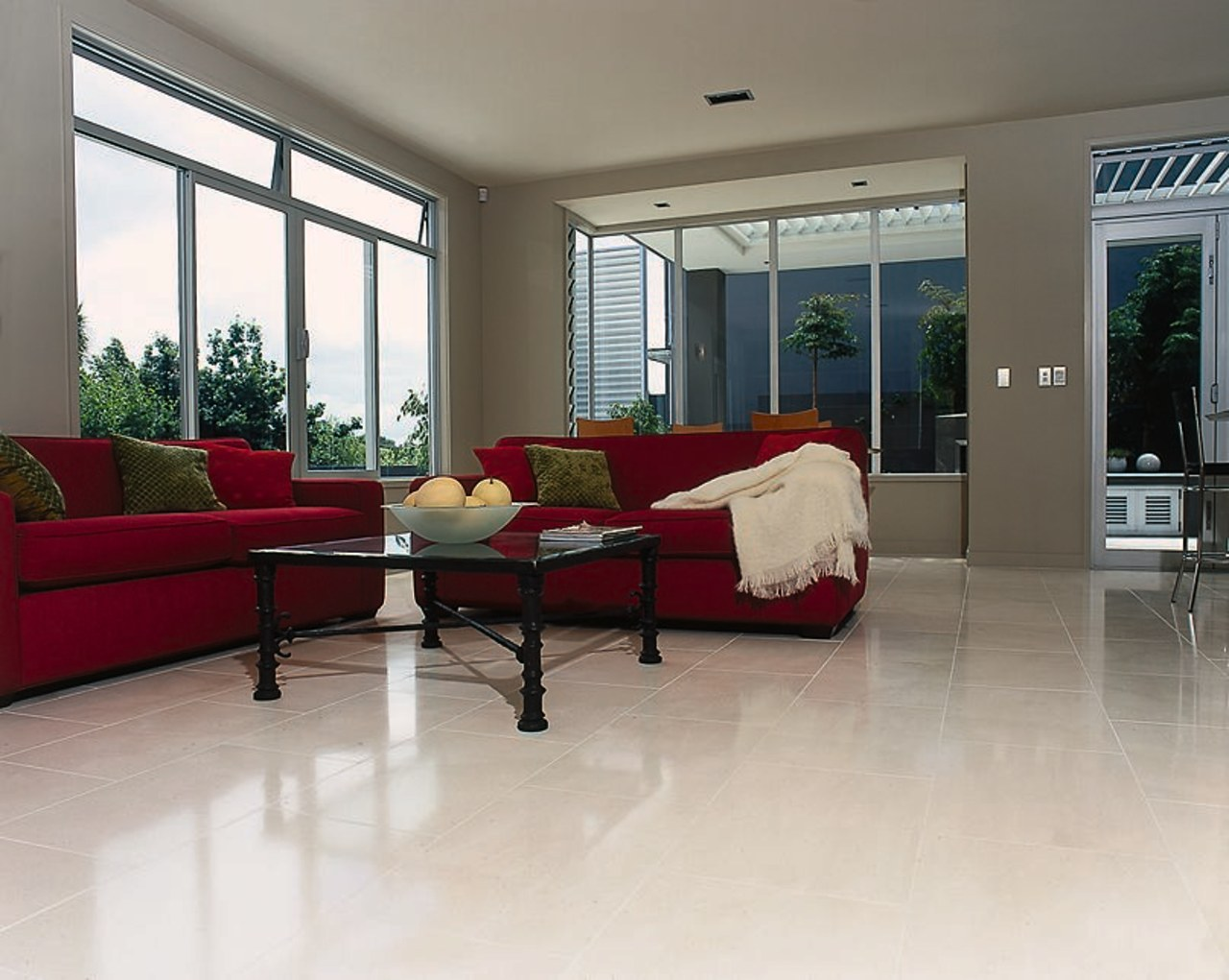 A lounge area with red sofas, red and floor, flooring, hardwood, home, house, interior design, laminate flooring, living room, property, real estate, room, window, wood, wood flooring, gray, white