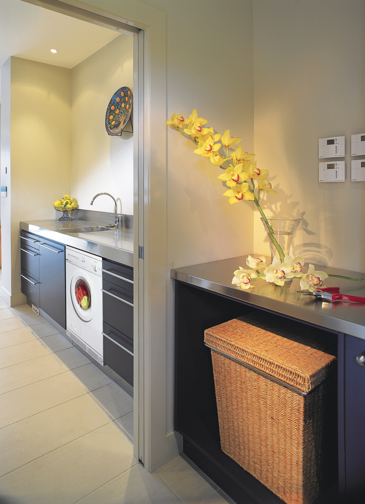 A laundry featuring a Smeg dryer. The laundry countertop, home appliance, interior design, kitchen, major appliance, room, gray, orange