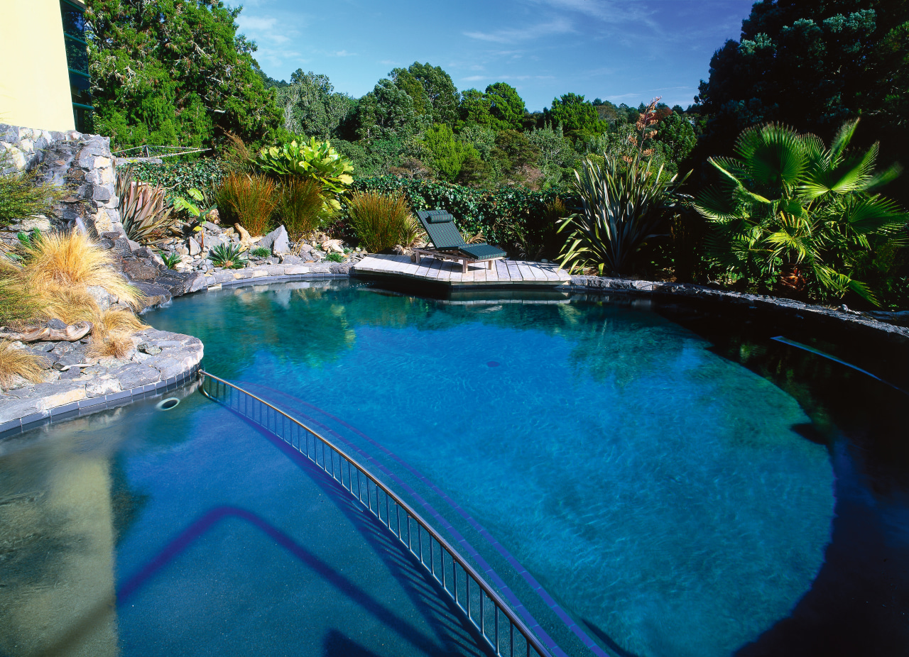 Round black pool in natural setting with stone leisure, pond, reflection, resort, swimming pool, tree, water, water feature, water resources, watercourse, blue