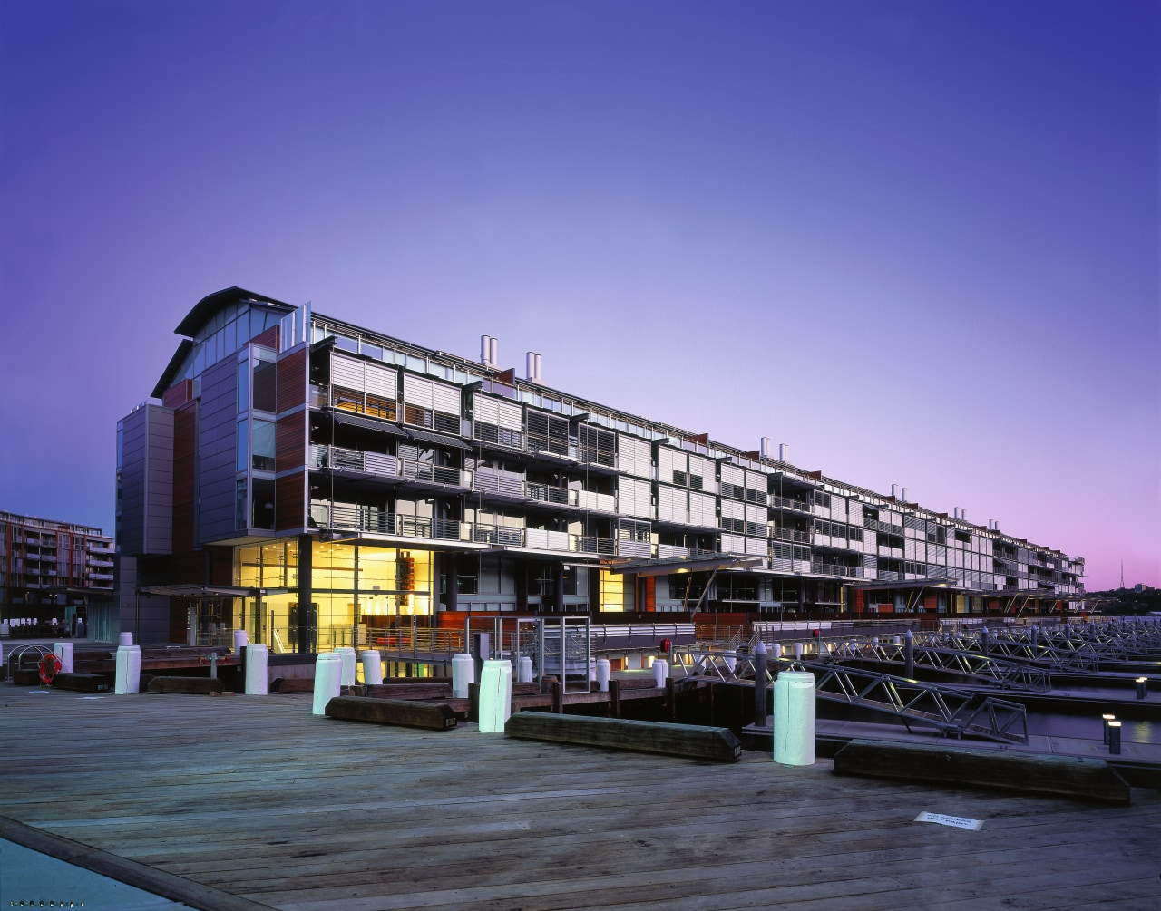 view of apartments located on the pier architecture, building, city, condominium, corporate headquarters, evening, facade, metropolis, metropolitan area, mixed use, reflection, residential area, sky, blue
