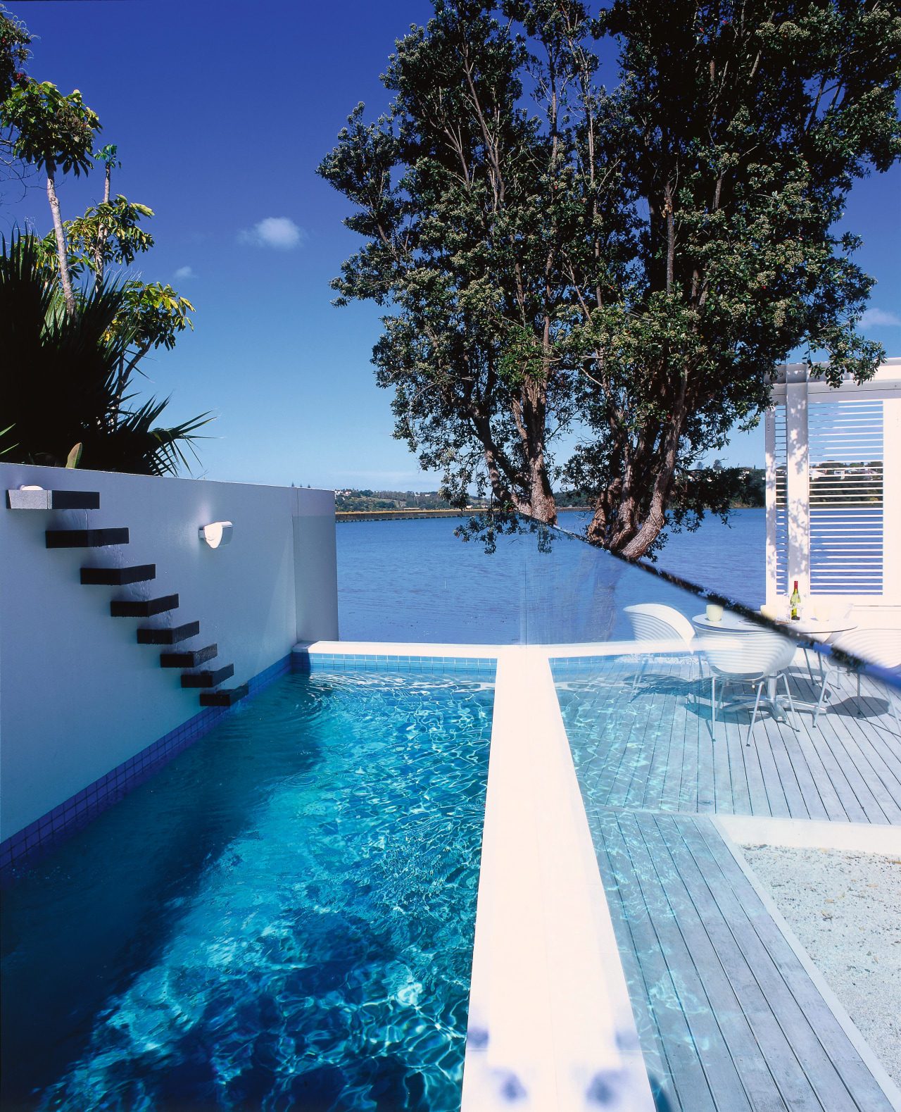 View of long blue pool with white surrounds, architecture, condominium, daytime, estate, home, house, leisure, property, real estate, reflection, resort, sky, swimming pool, tree, water, blue