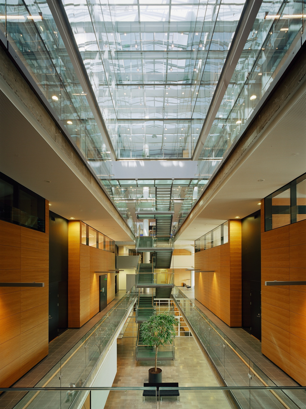 An interior view of the building. apartment, architecture, ceiling, condominium, daylighting, glass, headquarters, interior design, lobby, metropolitan area, real estate, brown, gray