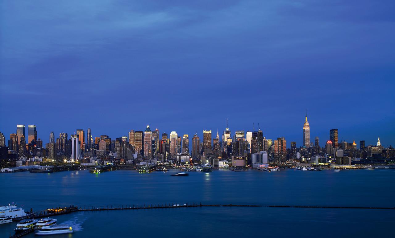 view of the manhattan CBd skyline accross the city, cityscape, daytime, downtown, dusk, evening, horizon, landmark, metropolis, metropolitan area, night, reflection, sea, sky, skyline, skyscraper, tower block, urban area, water, blue