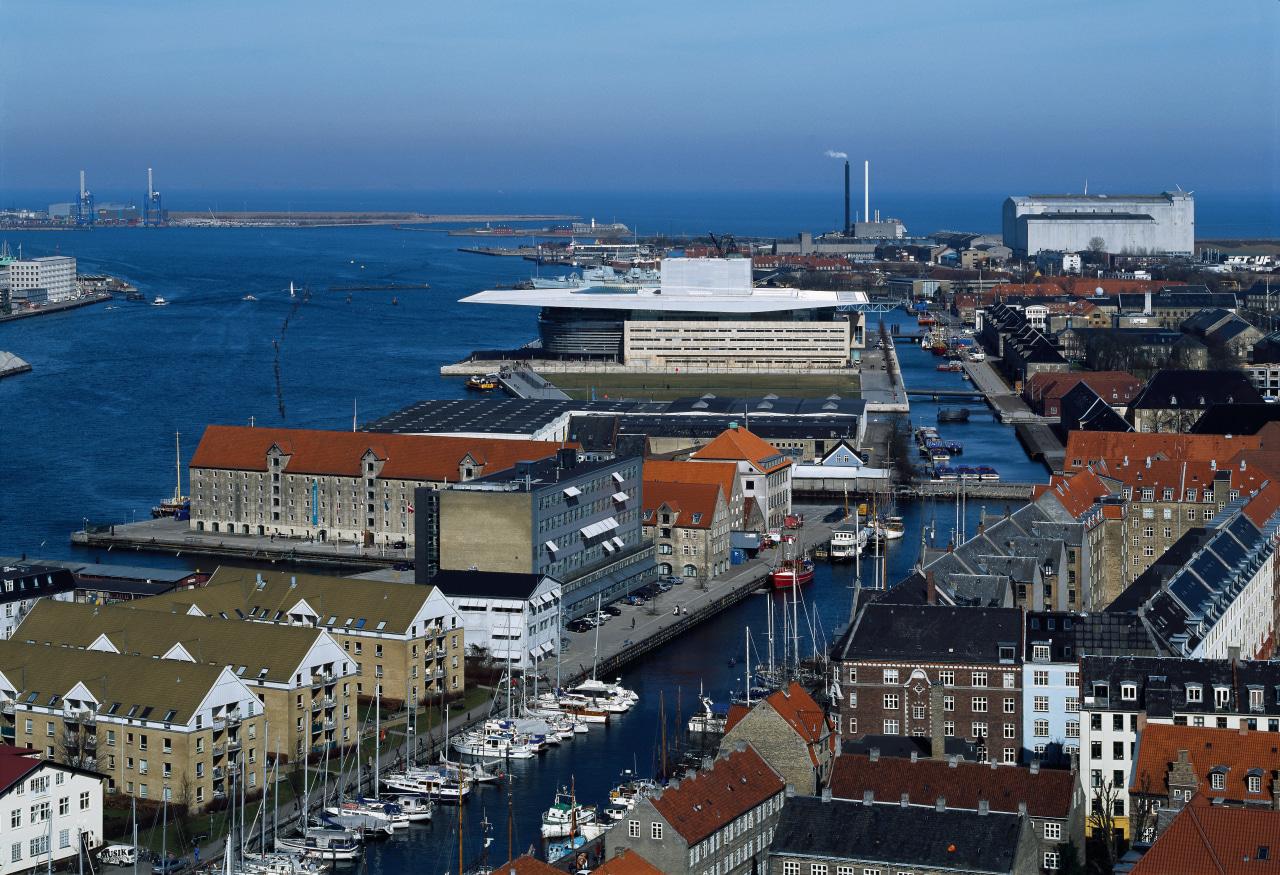 An aerial view of the opera house. aerial photography, bird's eye view, city, cityscape, harbor, marina, passenger ship, port, sea, ship, sky, urban area