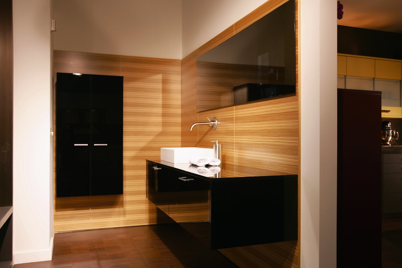 A view of a bathroom by Poggenphol. architecture, bathroom, cabinetry, floor, flooring, furniture, interior design, room, wood, brown, black