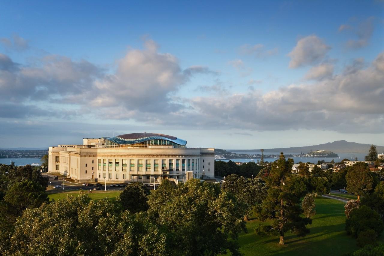 A view of the Auckalnd war memorial museum architecture, building, city, cloud, daytime, estate, home, horizon, landmark, meteorological phenomenon, real estate, sky, skyline, tree, gray, teal
