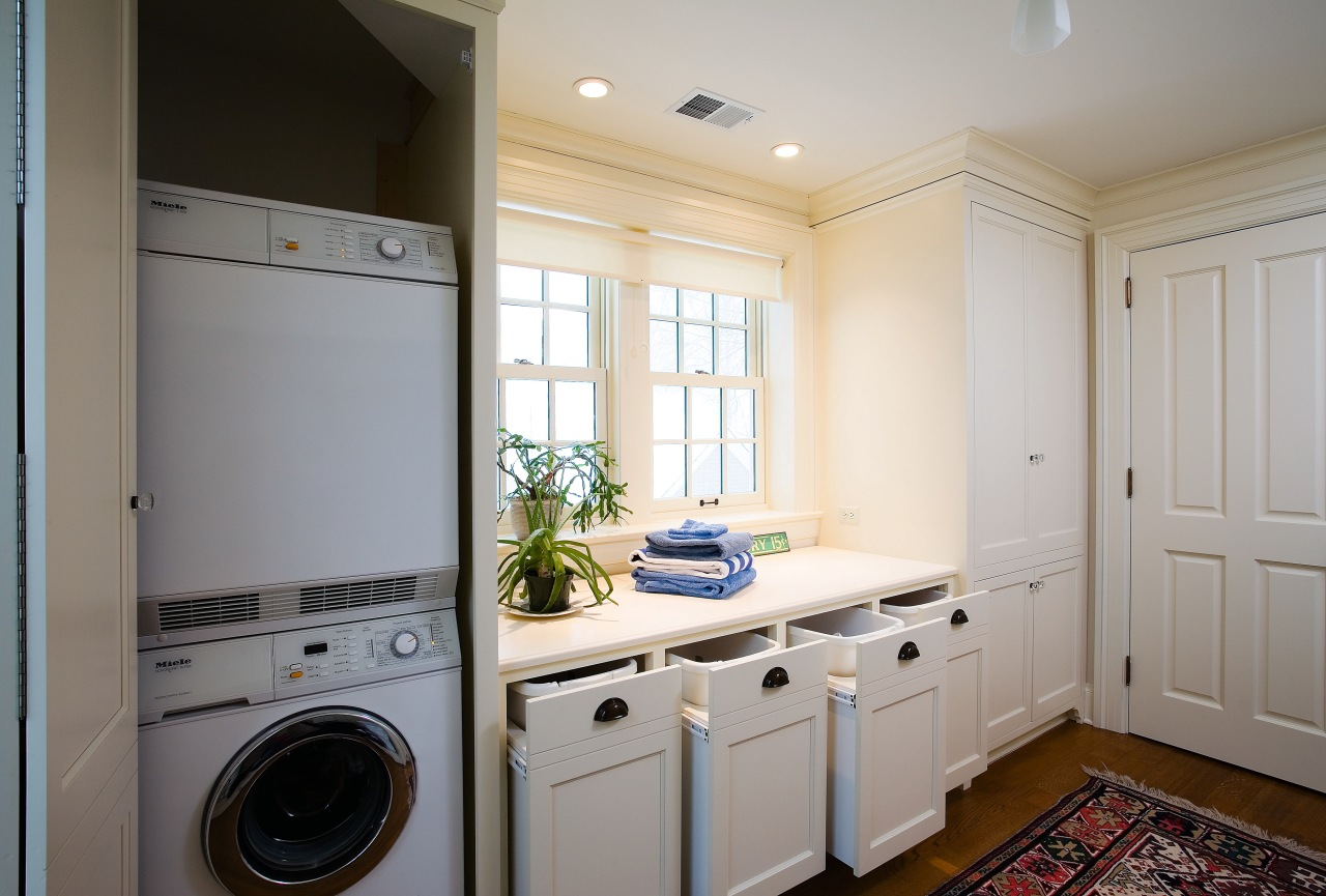 A view of this laundry featuring white timber cabinetry, clothes dryer, countertop, floor, home, home appliance, kitchen, laundry, laundry room, major appliance, room, washing machine, gray