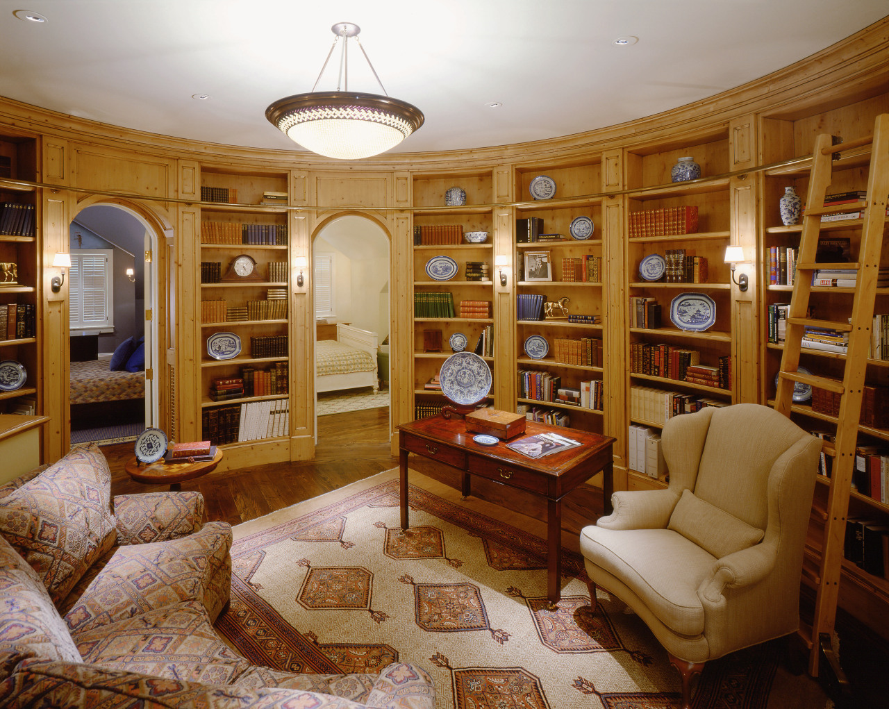 A view of the library featuring timber shelving, bookcase, ceiling, estate, furniture, home, interior design, library, living room, property, real estate, brown