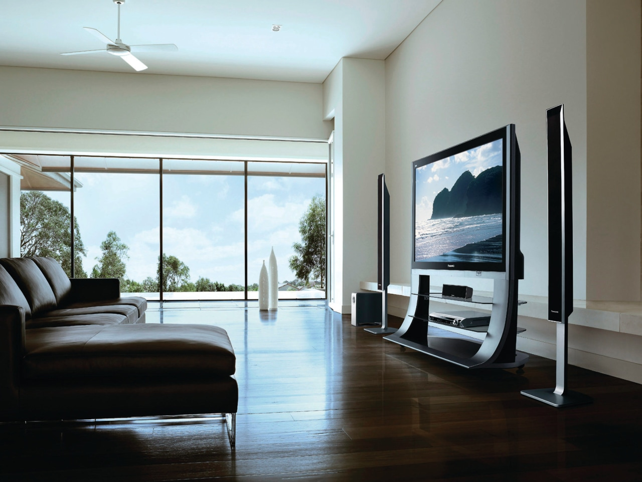 A view of this contemporary living area featuring door, floor, flooring, furniture, hardwood, interior design, living room, real estate, room, window, wood flooring, gray, black, white