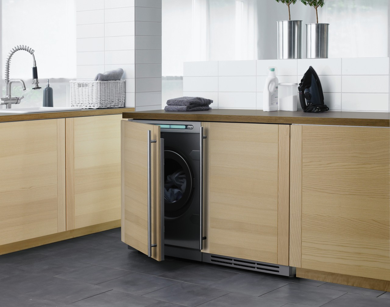 A view of this clean, contemporary laundry featuring cabinetry, clothes dryer, countertop, floor, furniture, home appliance, kitchen, kitchen appliance, kitchen stove, major appliance, product, product design, refrigerator, washing machine, white