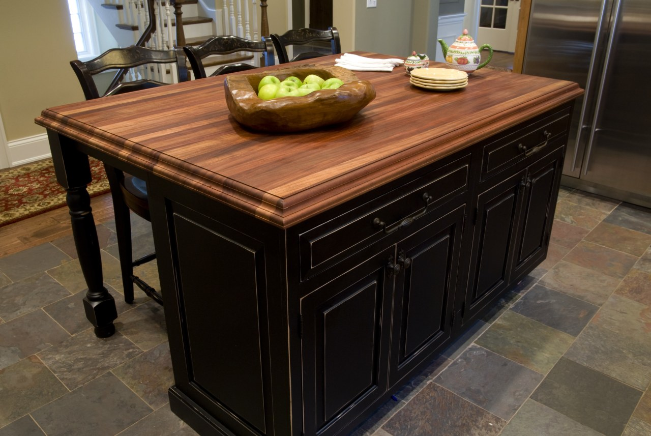 A solid mahogany countertop with black cabinetry of cabinetry, countertop, floor, flooring, furniture, hardwood, kitchen, table, tile, wood stain, black, brown