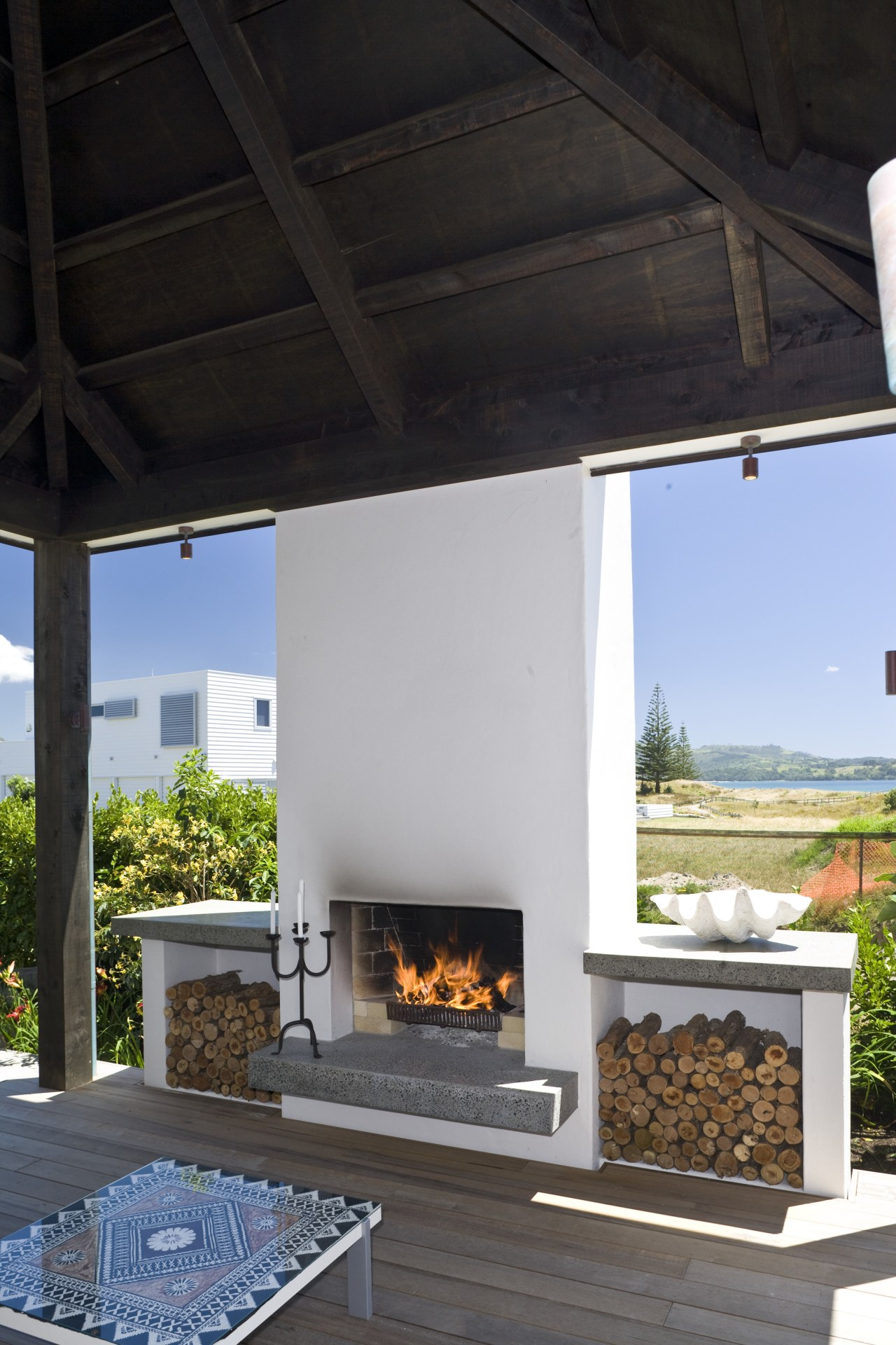 View of the deck with outdoor fireplace, decking, fireplace, hearth, black, gray