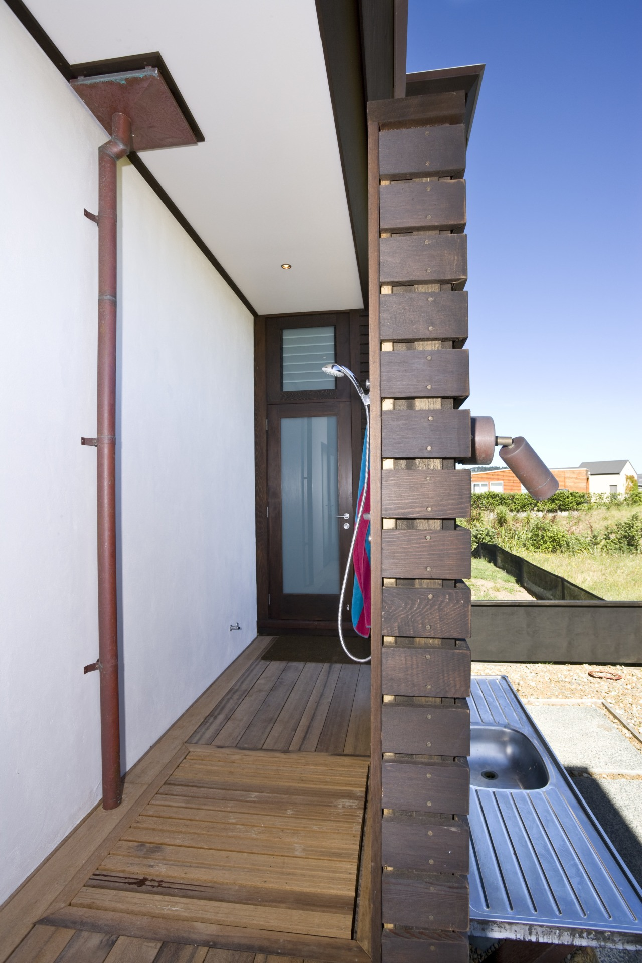 View of an outdoor shower, decking, shower fittings. architecture, daylighting, handrail, house, stairs, structure, wood, white