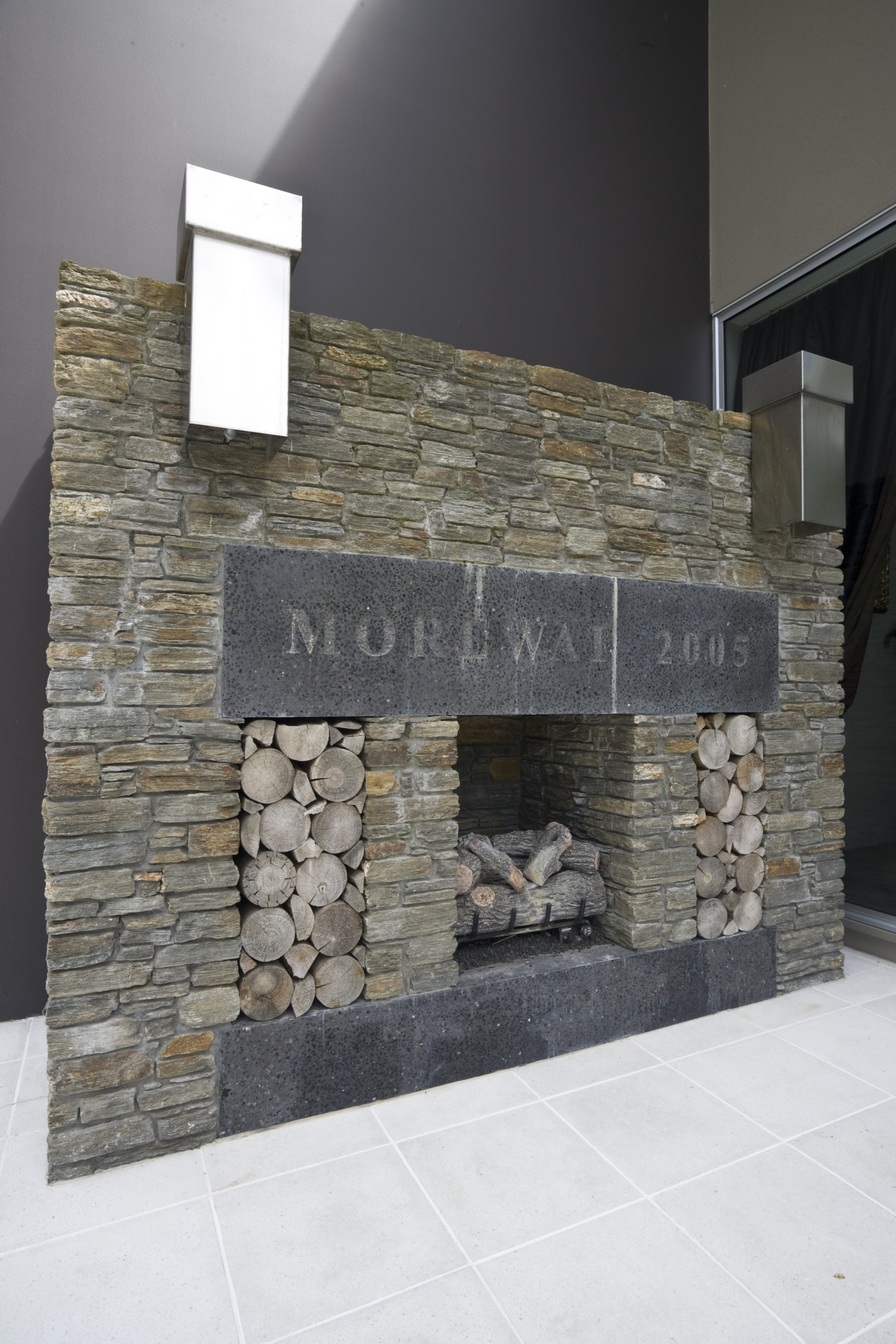 View of the outdoor fireplace framed in schist fireplace, hearth, stone wall, wall, gray, black, white
