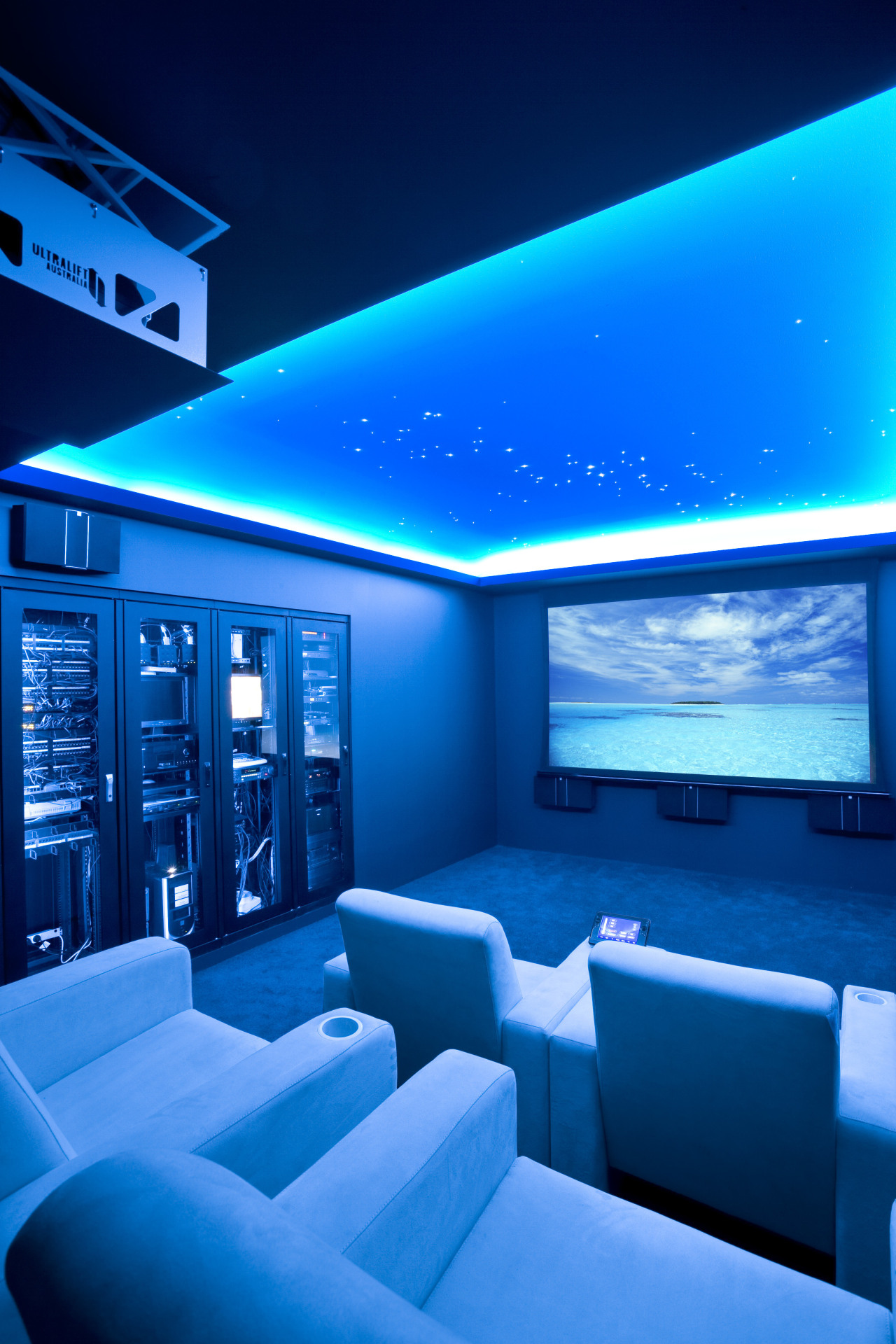 View of home cinema with projector screen, audiovisual architecture, blue, ceiling, display device, interior design, light, lighting, sky, technology, blue, teal