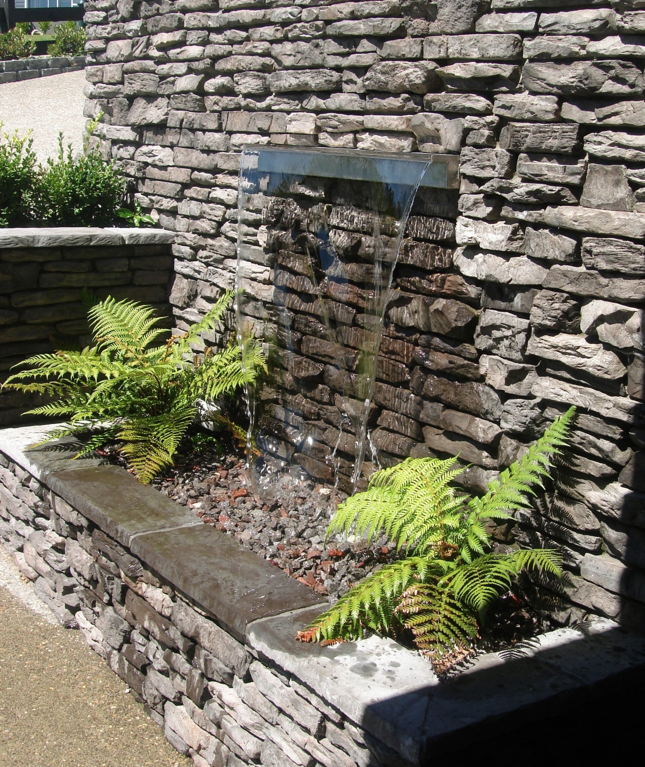 View of garden which includes a stone wall garden, grass, landscape, landscaping, outdoor structure, plant, stone wall, walkway, wall, gray, black