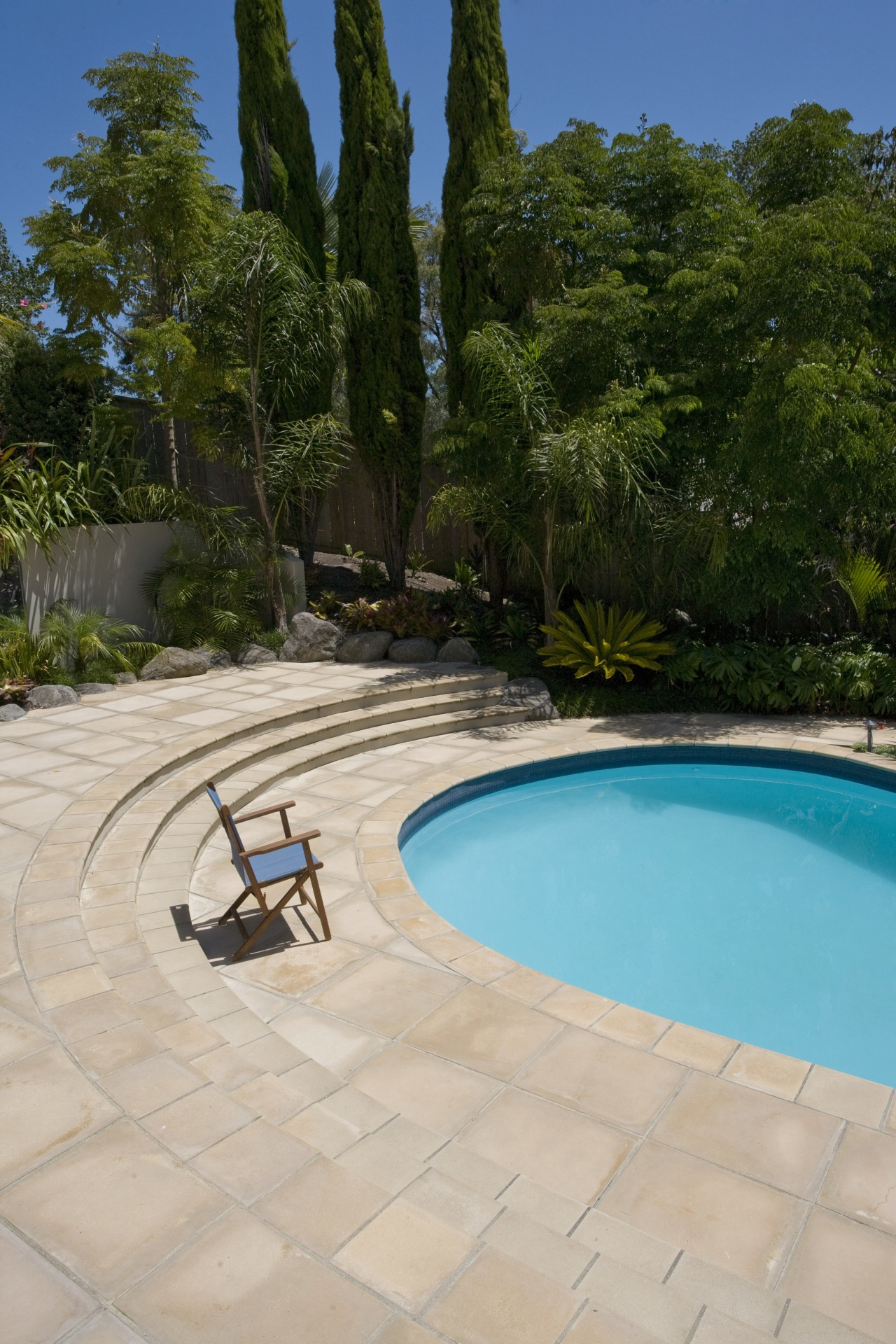 View of a pool with paving that features backyard, estate, landscape, leisure, outdoor structure, property, real estate, swimming pool, tree, vacation, water, gray