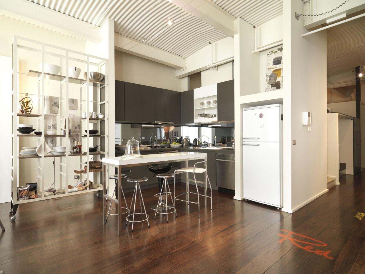 View of kitchen area with dark-stained timber flooring, floor, flooring, interior design, kitchen, loft, wood flooring, white, brown