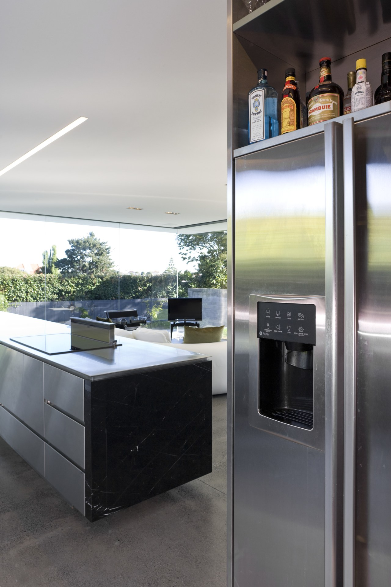 View of open-plan kitchen featuring polished concrete flooring, countertop, home appliance, interior design, kitchen, major appliance, white, black, gray