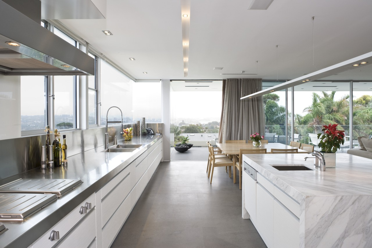 View of the kitchen area which features an architecture, countertop, house, interior design, kitchen, real estate, window, white, gray