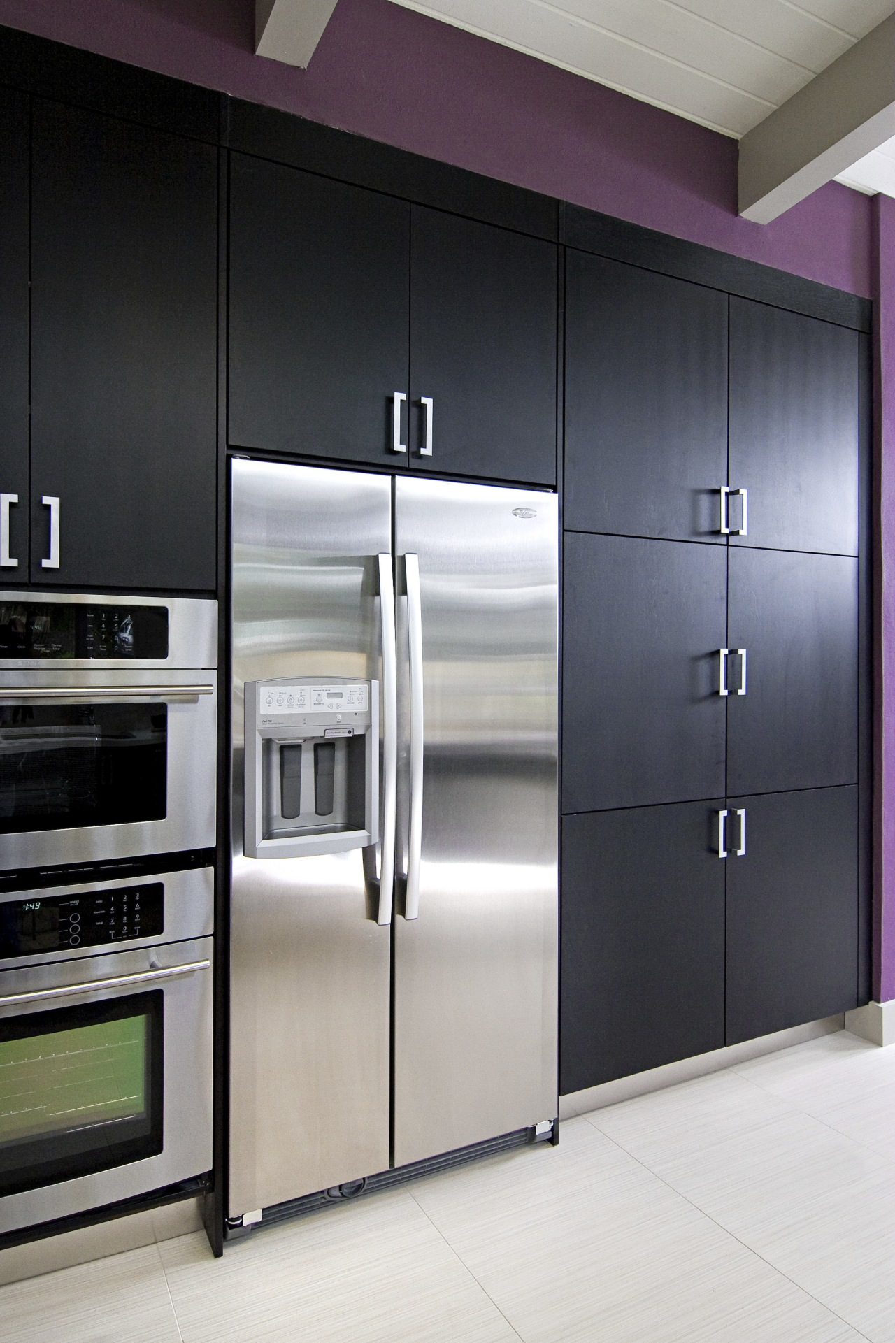 View of a remodeled kitchen which features dark cabinetry, home appliance, interior design, kitchen, major appliance, refrigerator, wardrobe, gray, black
