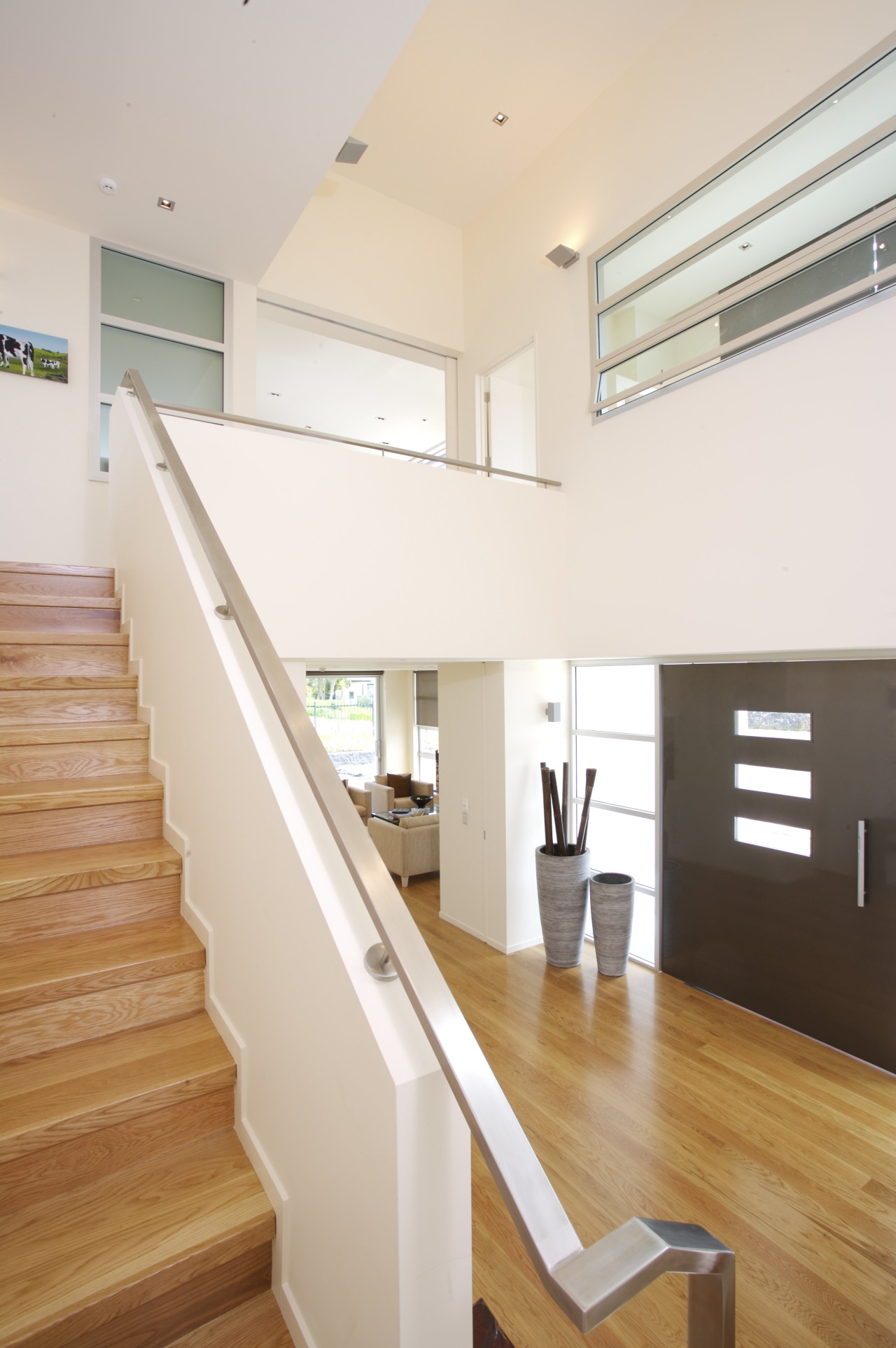 interior stairs view of a new home in architecture, ceiling, daylighting, floor, flooring, handrail, hardwood, home, house, interior design, laminate flooring, property, real estate, stairs, wall, window, wood, wood flooring, white