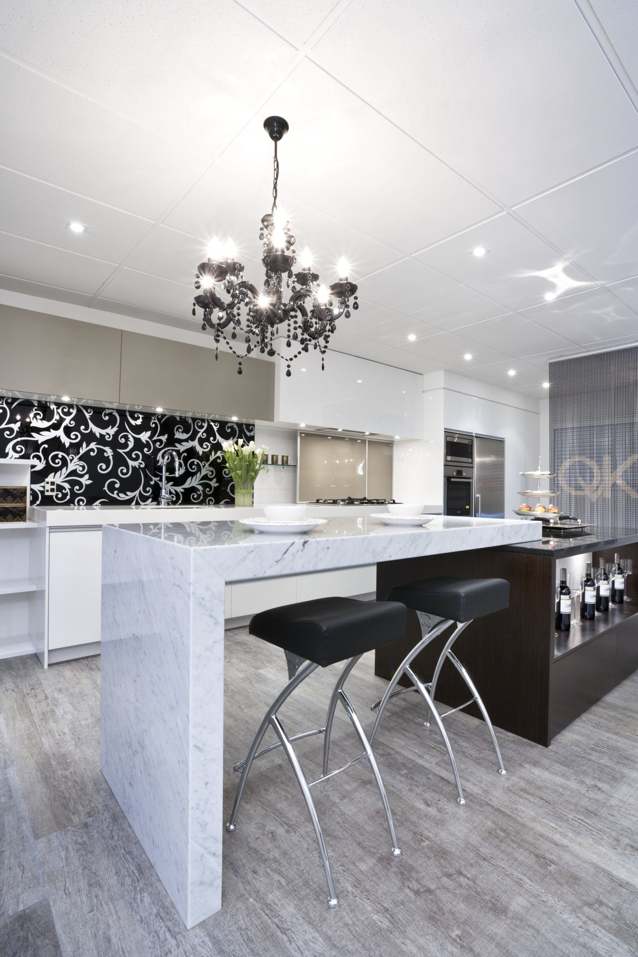 This kitchen by Yellowfox features an island with architecture, ceiling, chair, dining room, floor, flooring, furniture, interior design, kitchen, light fixture, product design, table, wall, gray, white