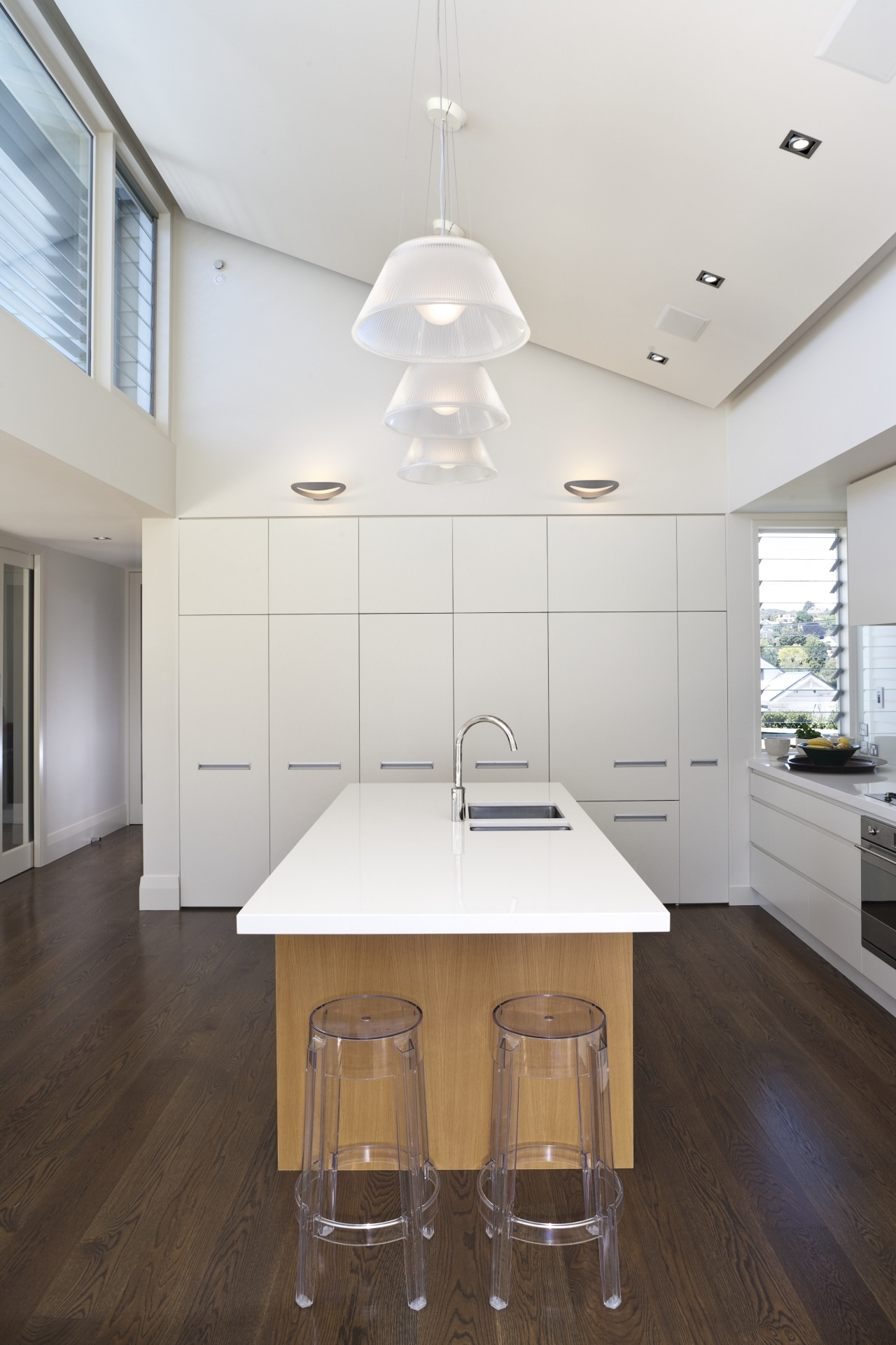 Sleek white lacquered cabinetry wraps the sides of ceiling, countertop, daylighting, floor, flooring, hardwood, home, house, interior design, kitchen, laminate flooring, real estate, room, table, wood flooring, white