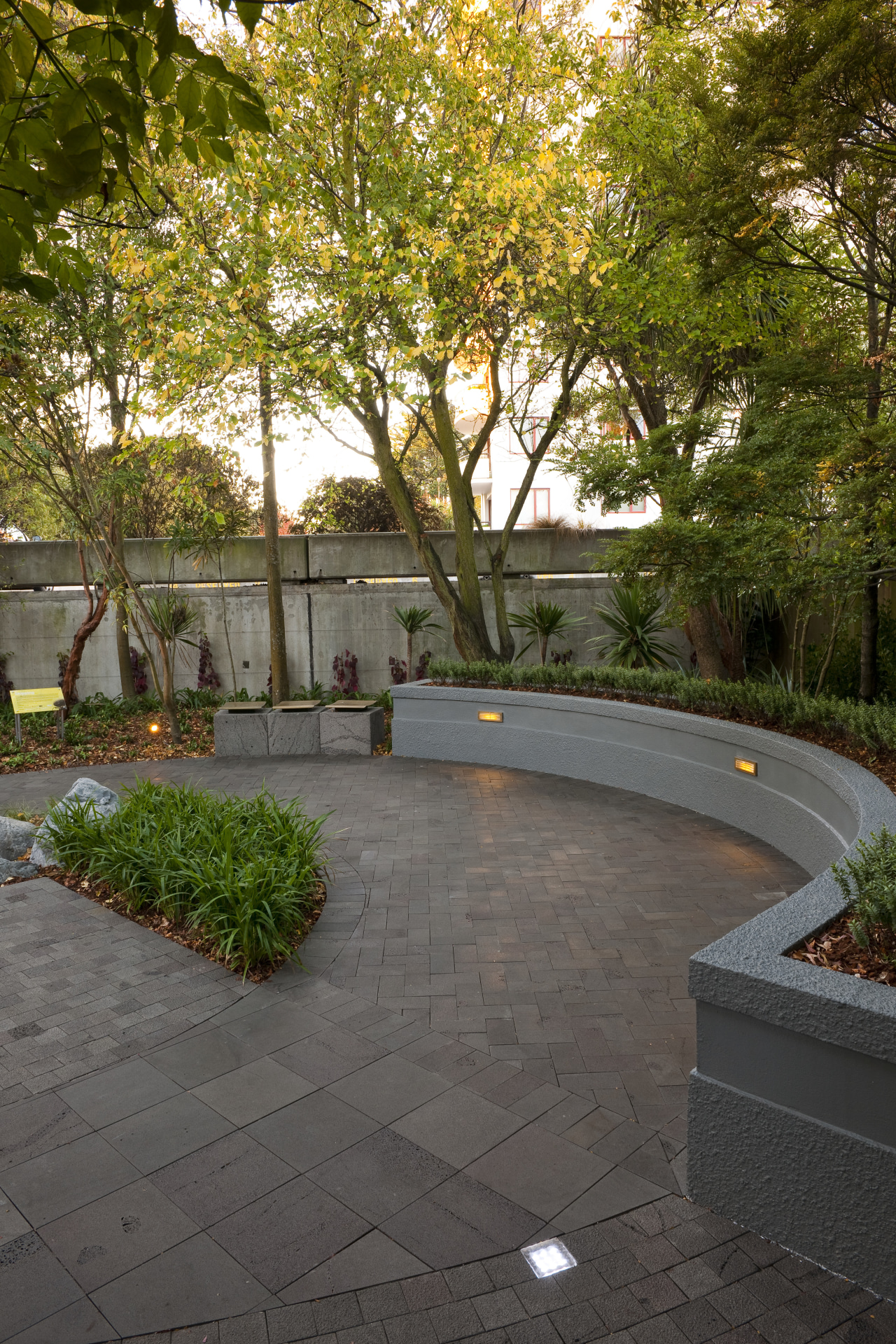 View of private courtyard which features native planting, architecture, backyard, courtyard, estate, garden, grass, landscape, landscaping, leaf, outdoor structure, patio, plant, real estate, residential area, road surface, tree, walkway, wall, yard, brown, gray