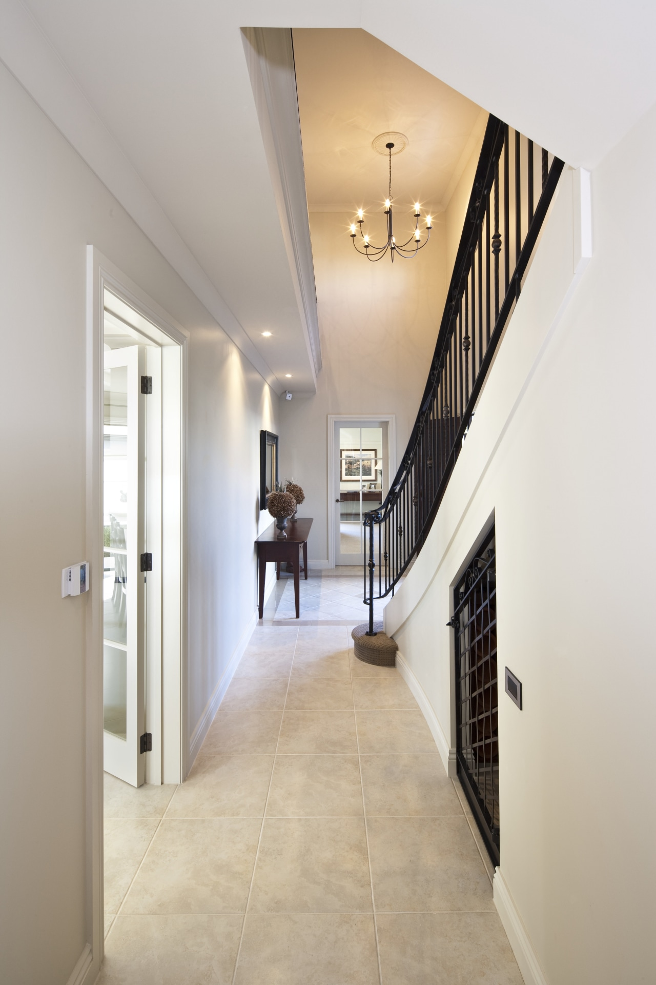 View of a hallway with tiled floors. apartment, architecture, ceiling, daylighting, estate, floor, flooring, hall, handrail, home, house, interior design, lobby, property, real estate, stairs, wall, wood flooring, gray