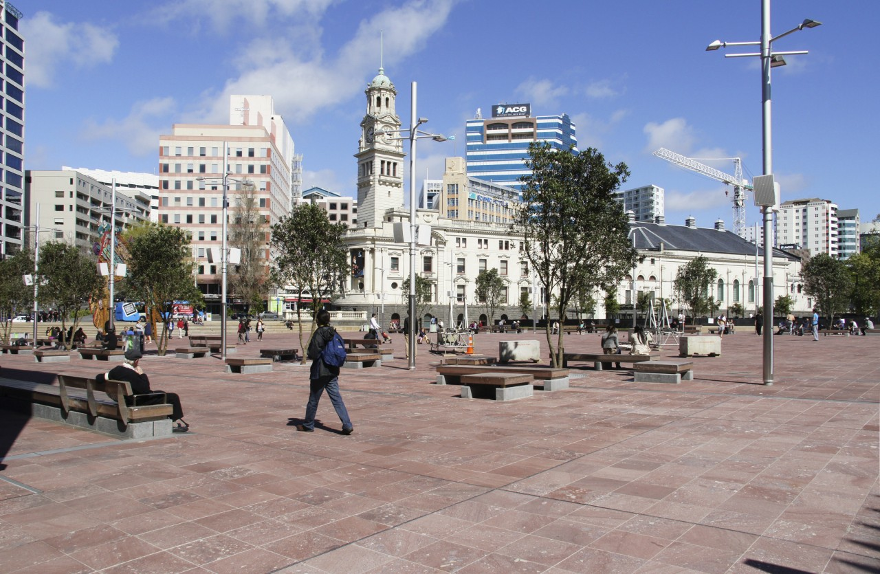 View of Aotea Square which features paving, planters, city, daytime, downtown, metropolis, metropolitan area, mixed use, neighbourhood, outdoor structure, plaza, public space, sky, town, town square, tree, urban area, walkway, gray, teal