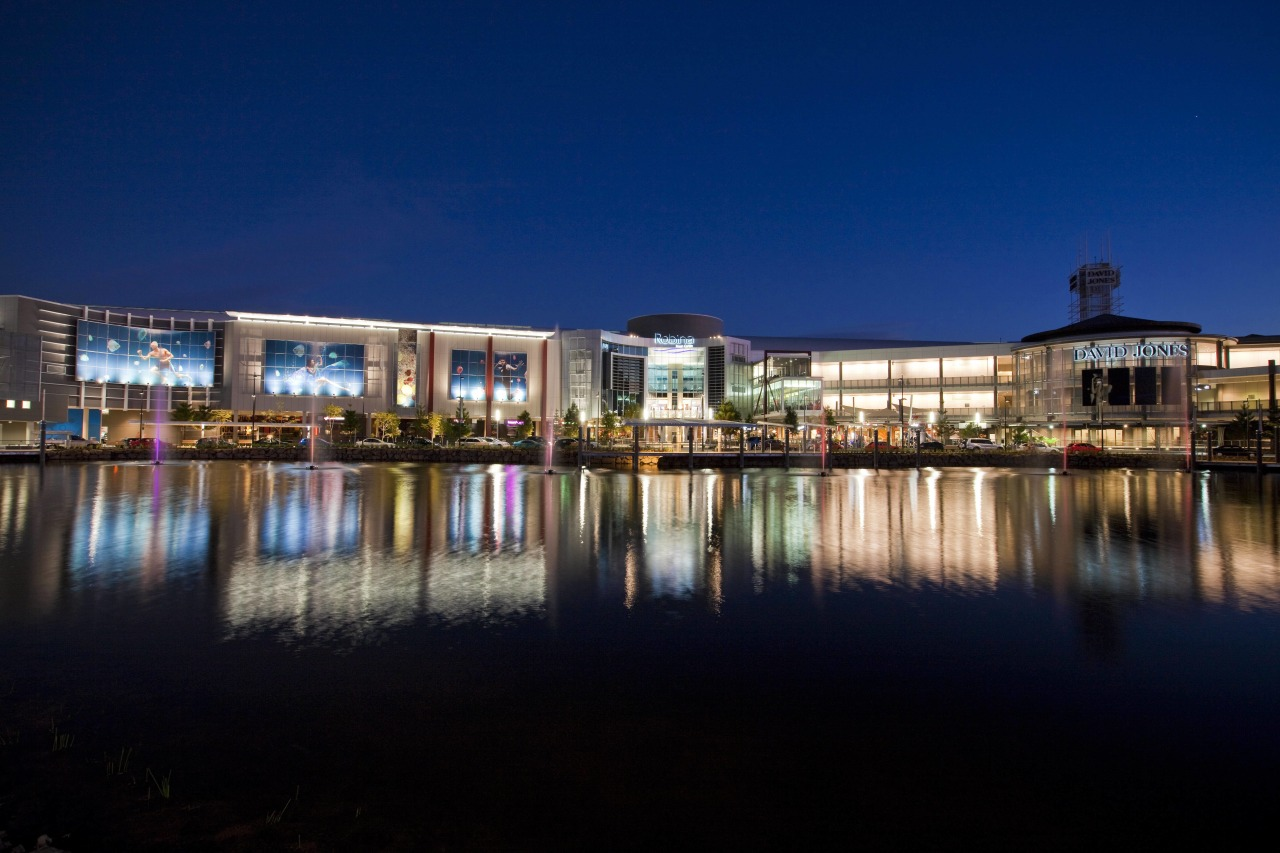 Exterior view of the Robina Town Centre where architecture, city, cityscape, dusk, estate, evening, home, hotel, lighting, mixed use, night, real estate, reflection, residential area, sky, tourist attraction, water, blue, black