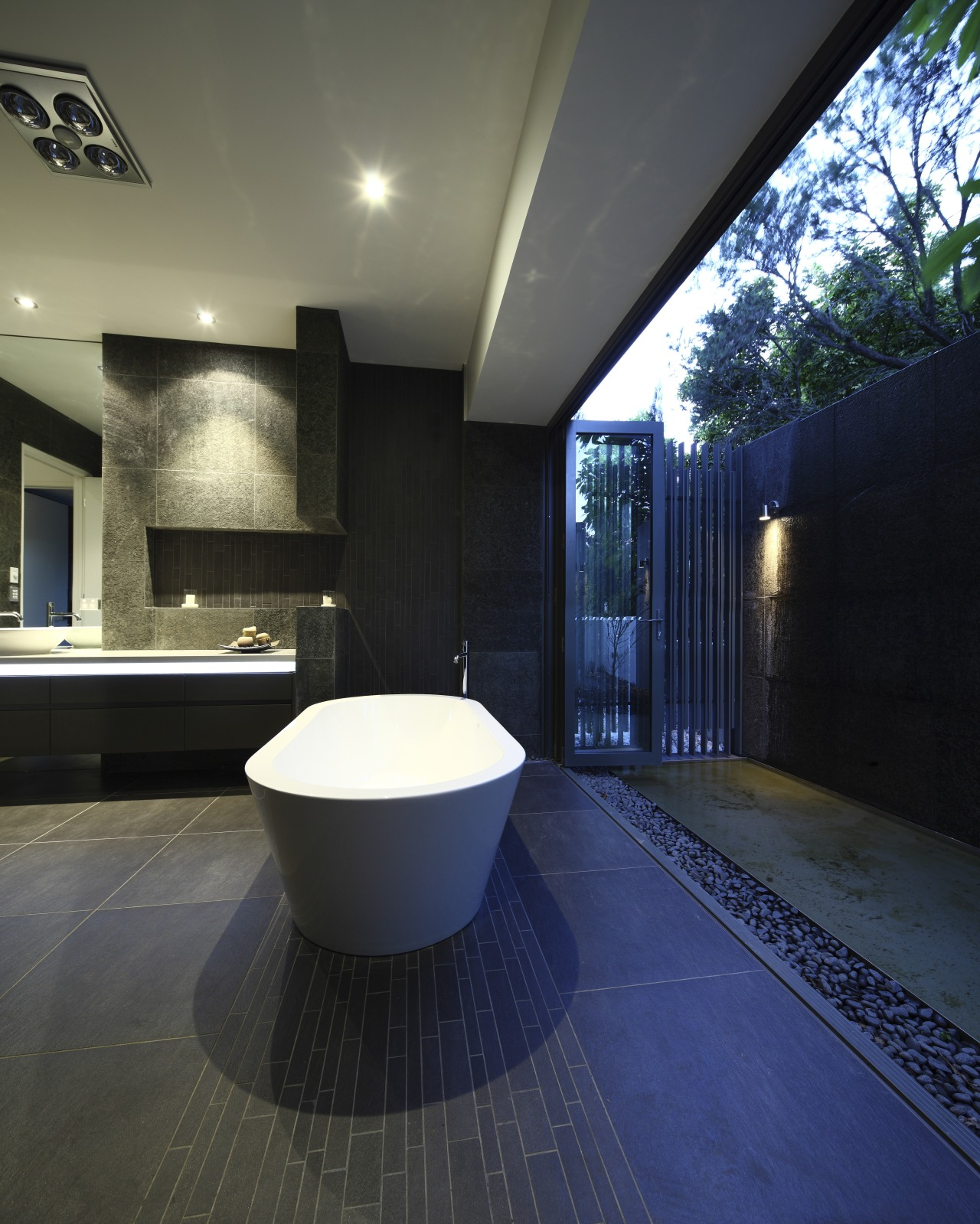 View of dark-toned bathroom with white tub. architecture, bathroom, ceiling, daylighting, estate, floor, flooring, home, house, interior design, lighting, property, real estate, tile, black, blue