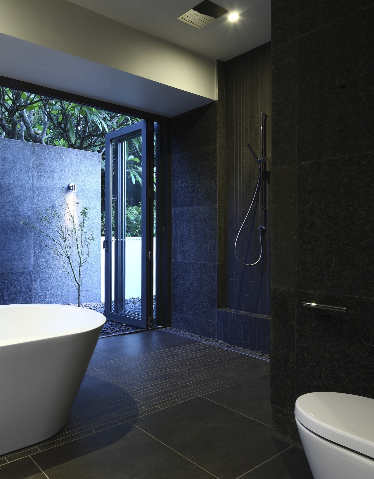 View of dark-toned bathroom with white tub. architecture, bathroom, ceiling, daylighting, floor, flooring, glass, home, interior design, room, tile, wall, black