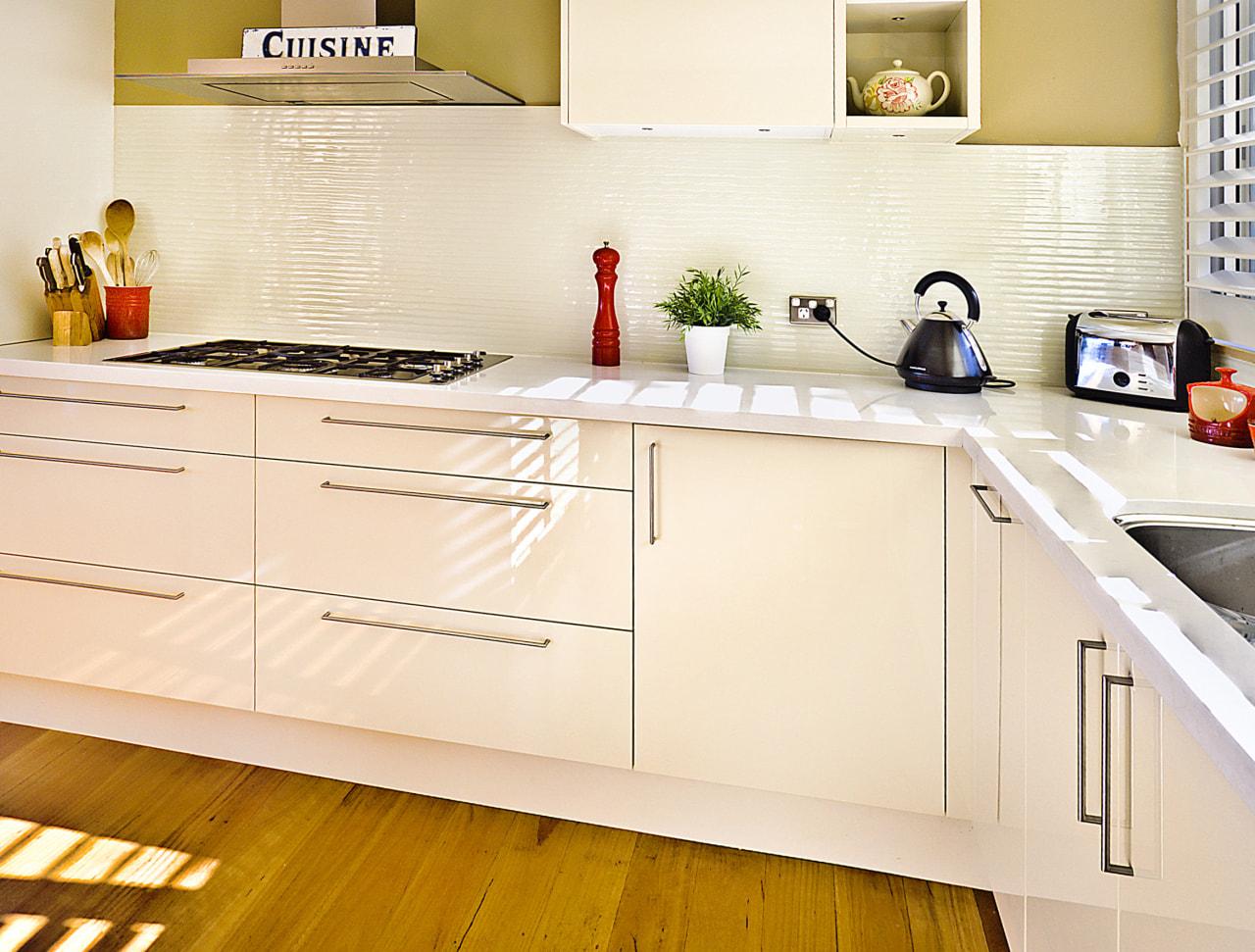 View of kitchen featuring wood floors, white bench cabinetry, countertop, cuisine classique, floor, flooring, hardwood, interior design, kitchen, product design, room, orange