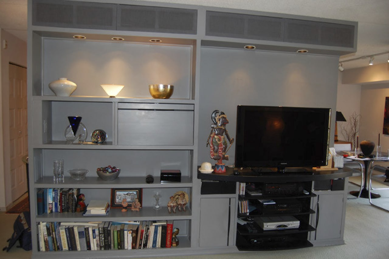 This home was remodeled by Forma Inc. A bookcase, furniture, home, interior design, living room, room, shelf, shelving, gray, black